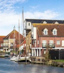 row of buildings beside a body of water in Faversham